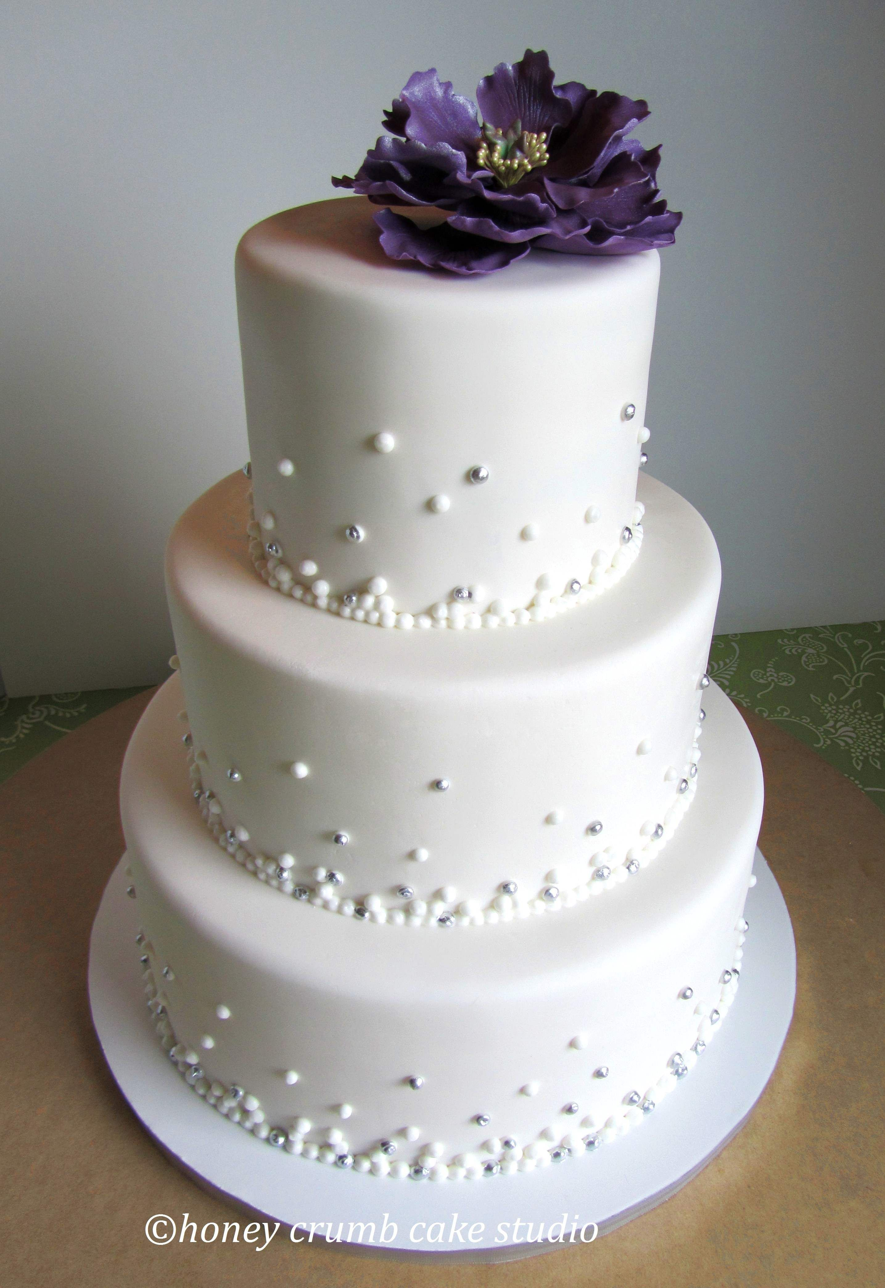 Three-tiered wedding cake for a reception at the Space Needle, Seattle, WA. 'Champagne bubbles' piped with Royal Icing and accented here and there with edible silver luster. Sugar peony.