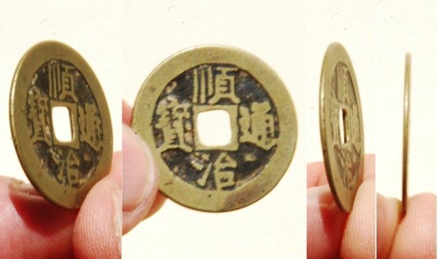 The front (obverse) side of a 'Shun Zhi Tong Bao' (顺治通寶) brass 1 cash coin cast from 1653-1657 AD by the Qing Dynasty Board of Works (BoW - 工部) Mint in Beijing during the reign of Emperor Shunzhi (1644-1661 AD).  The reverse side of this 'Yi Li' (one li = .0373 grams) series issue features the Chinese character 'Gong' indicating this coin was cast at the Gongbu Mint located in Beijing.  26mm in size; 4 grams in weight.   S-1391.