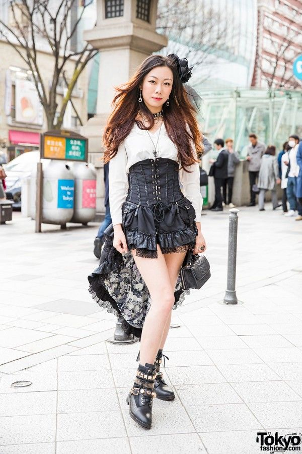 Serafina is a friendly student in black and white. She is wearing a white shirt with a corset dress that's short in the front and longer in the back. She accessorized with a headpiece, a choker and necklace, earrings, a snakeskin purse, rings and studded lace-up boots.