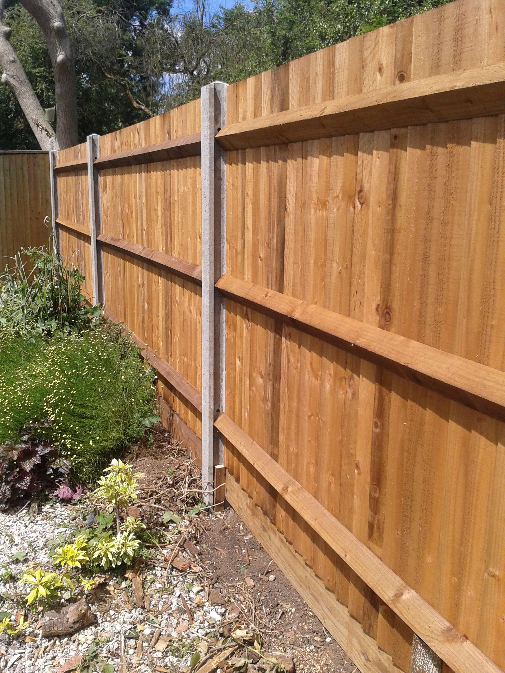 Close boarded fence with concrete posts and timber gravel boards