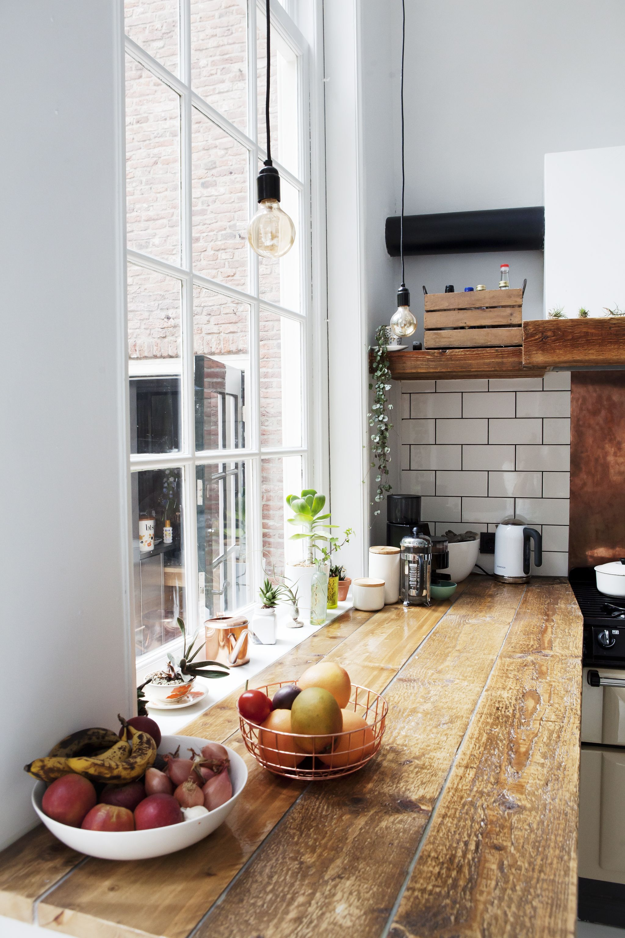 Industrial kitchen with wood countertops, white tile backsplash, and ...