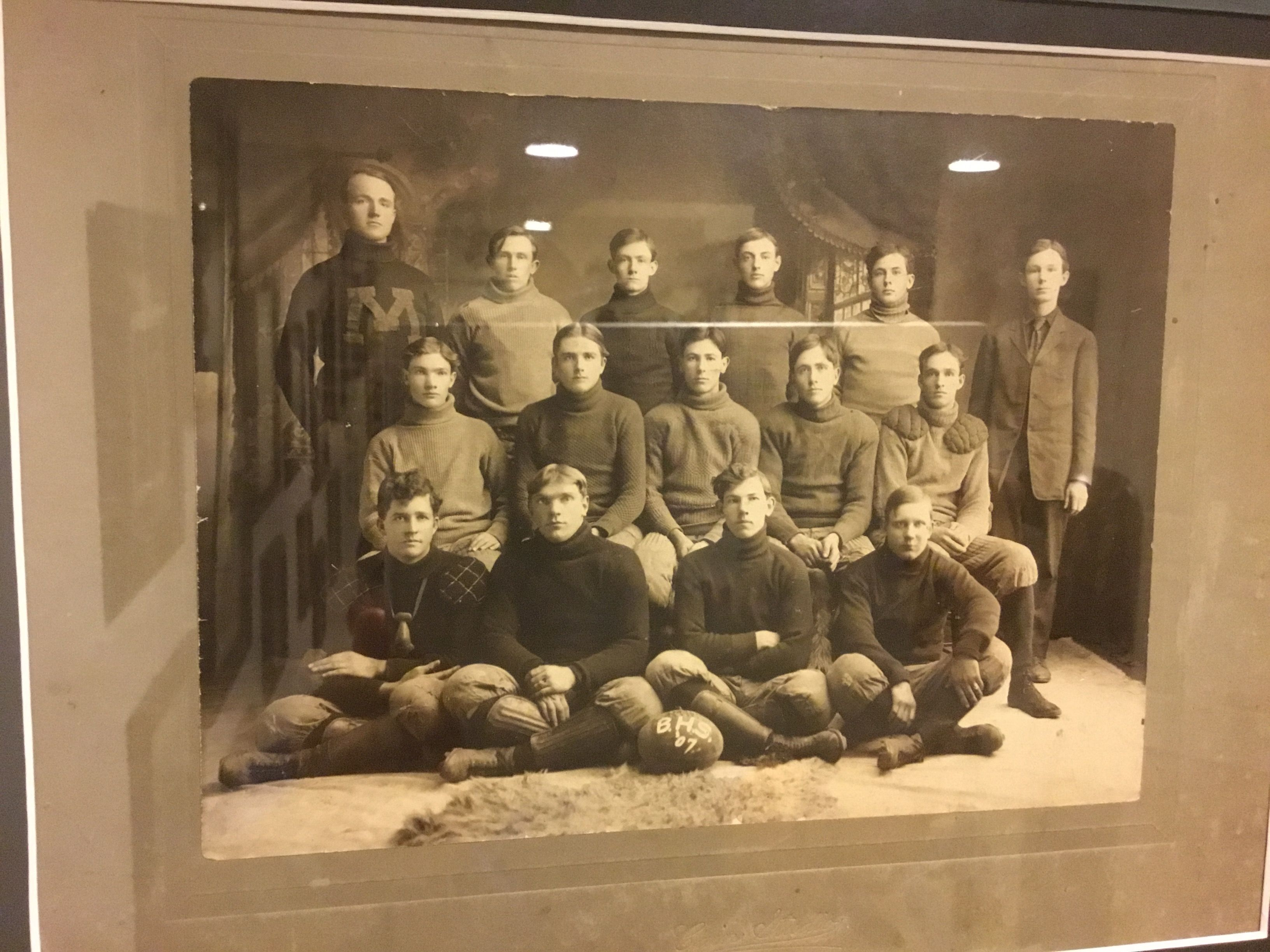 1907 football team including a player with nose guard and exterior shoulder pads, and shin guards.