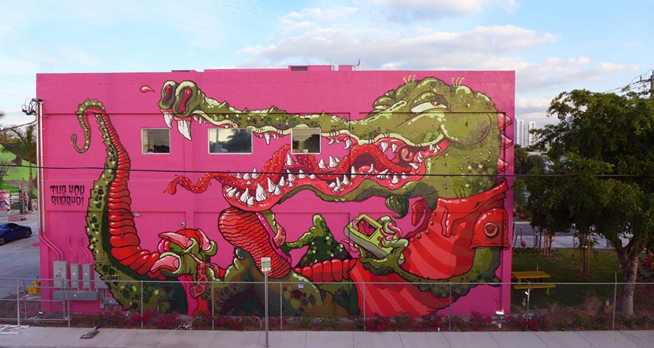 """Our friends Sheryo & The Yok, whose artwork we've covered on multiple occasions including 21st Precinct and their show at Superchief Gallery in LA, finished up a dope wall at the Miami Ad School during this year's Miami Art Basel. The piece, called """"Everglades Crocogator"""", is a trippy eye-gasm of pink, green, and red- nothing unusual from the pair."""