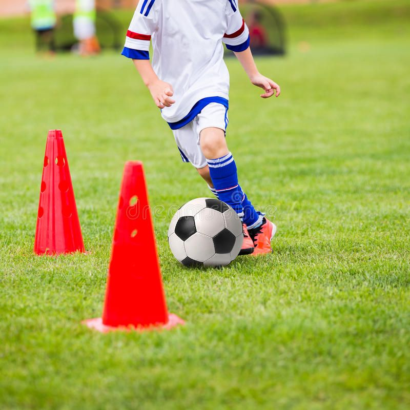 Kid playing soccer. Training football session for children