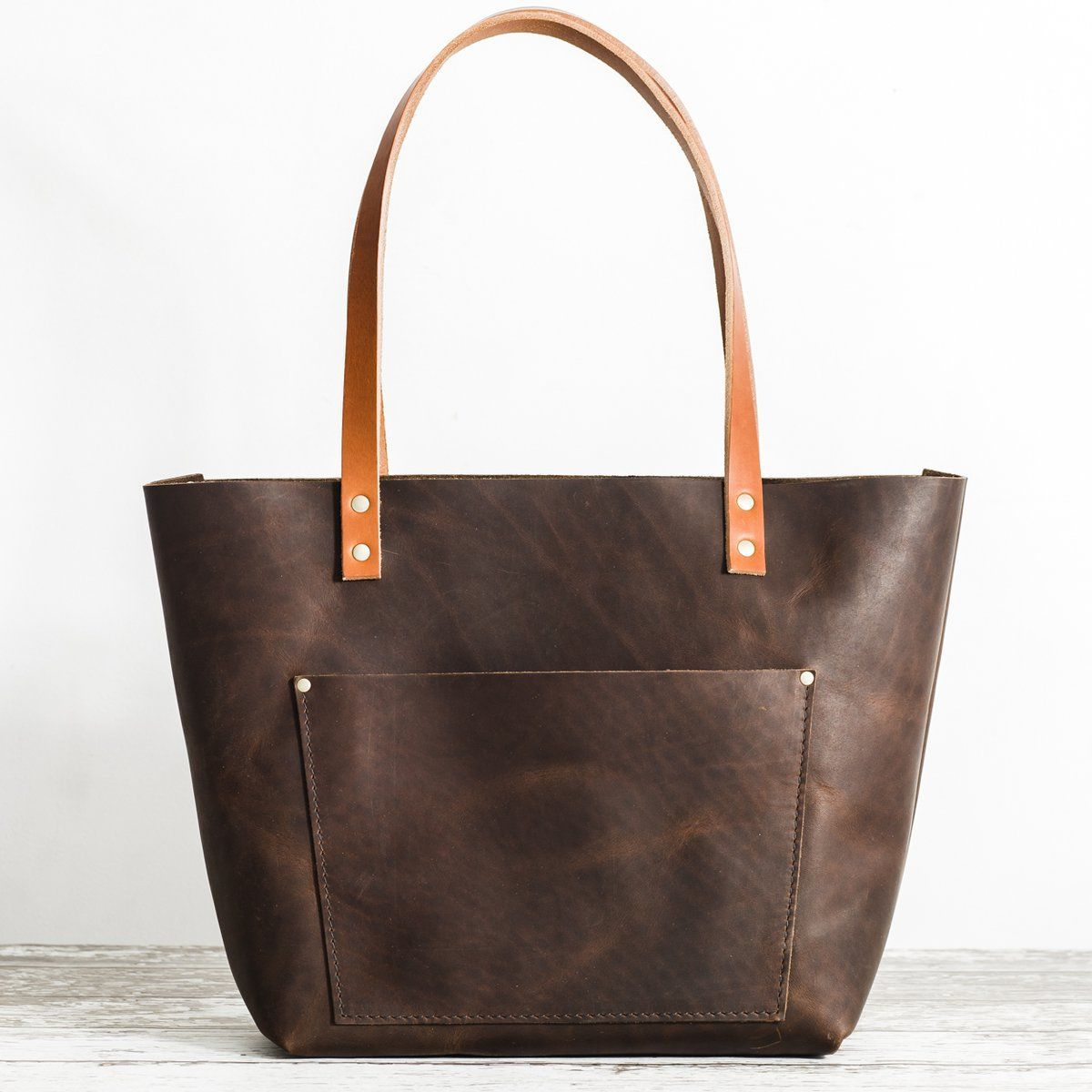72a7c757cff0 A dark brown leather tote bag with natural character