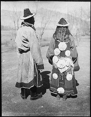 Phot: Rabden Lepcha, Coll: Sir Charles Bell, Date: End March or early April 1921, Region Lhasa.Golok region of Tibet at extreme east of Lhasa adjoining Amnye Machen mountain range. couple pictured may well have visited Lhasa to trade, but the fact that they wear their best long-sleeved 'Chuba' (gown) and travelling shrine  'gau' (amulet boxes) also indicate that their journey was a pilgrimage. On the woman's back are large engraved discs of silver,  turquoises and corals running down her…
