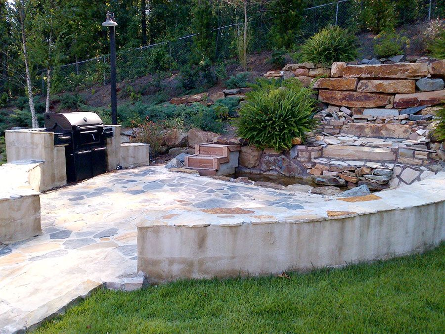 The Pocket Park At Heritage Parc Provides A Flowing Waterfall Beside An Outdoor Grill With Seating On The Surroundin Outdoor Custom Home Builders Outdoor Grill