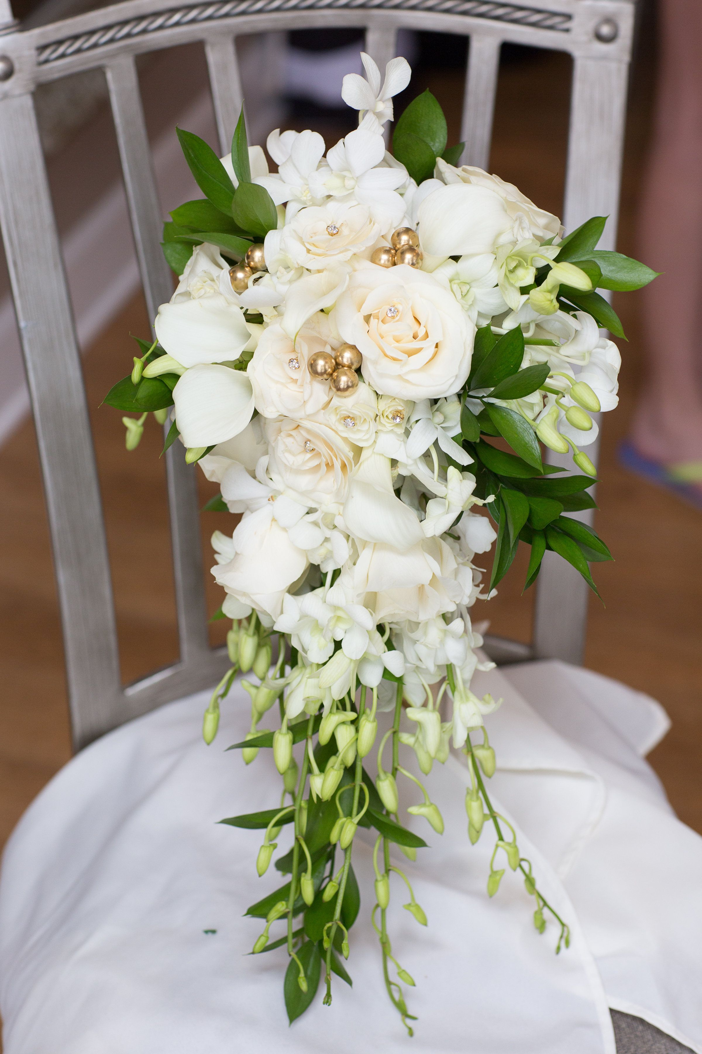 Calla lilies with roses and orchids in a cascade bouquet