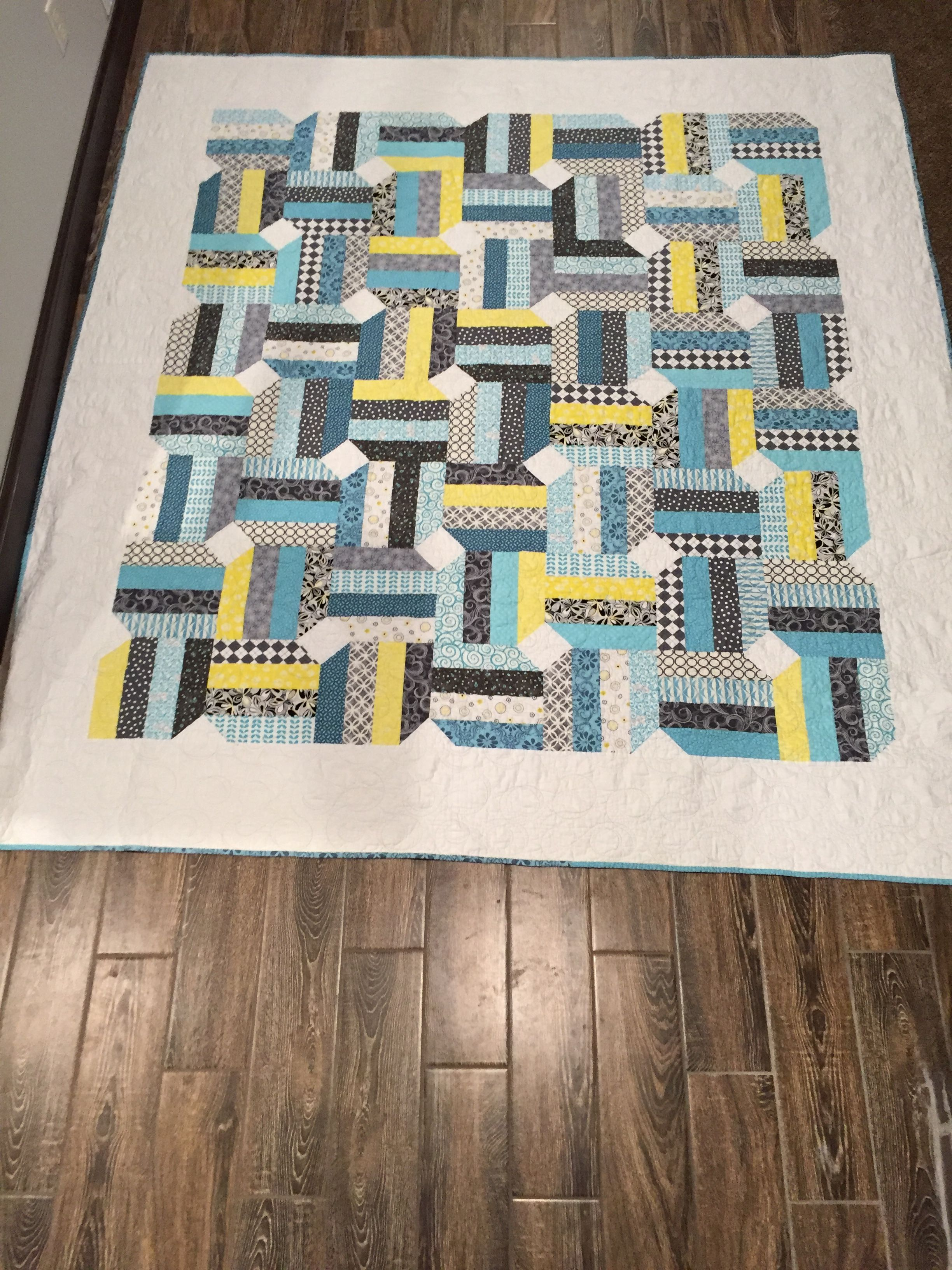 "Developed my own pattern for a rail fence quilt using 3"" strips and snowballing the corners. Great way to eliminate waste. 1/4 yard equals three strips. Given to Annalisa; she had requested this pattern with teals, greys and pop of yellow. (Patrick claims as his. LOL) 91"" X 104"". Given Christmas of 2013."