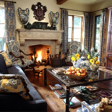 Chairs in indigo/cream print upholstery, fireplace, carved wooden heraldic crest, blue & white ceramics