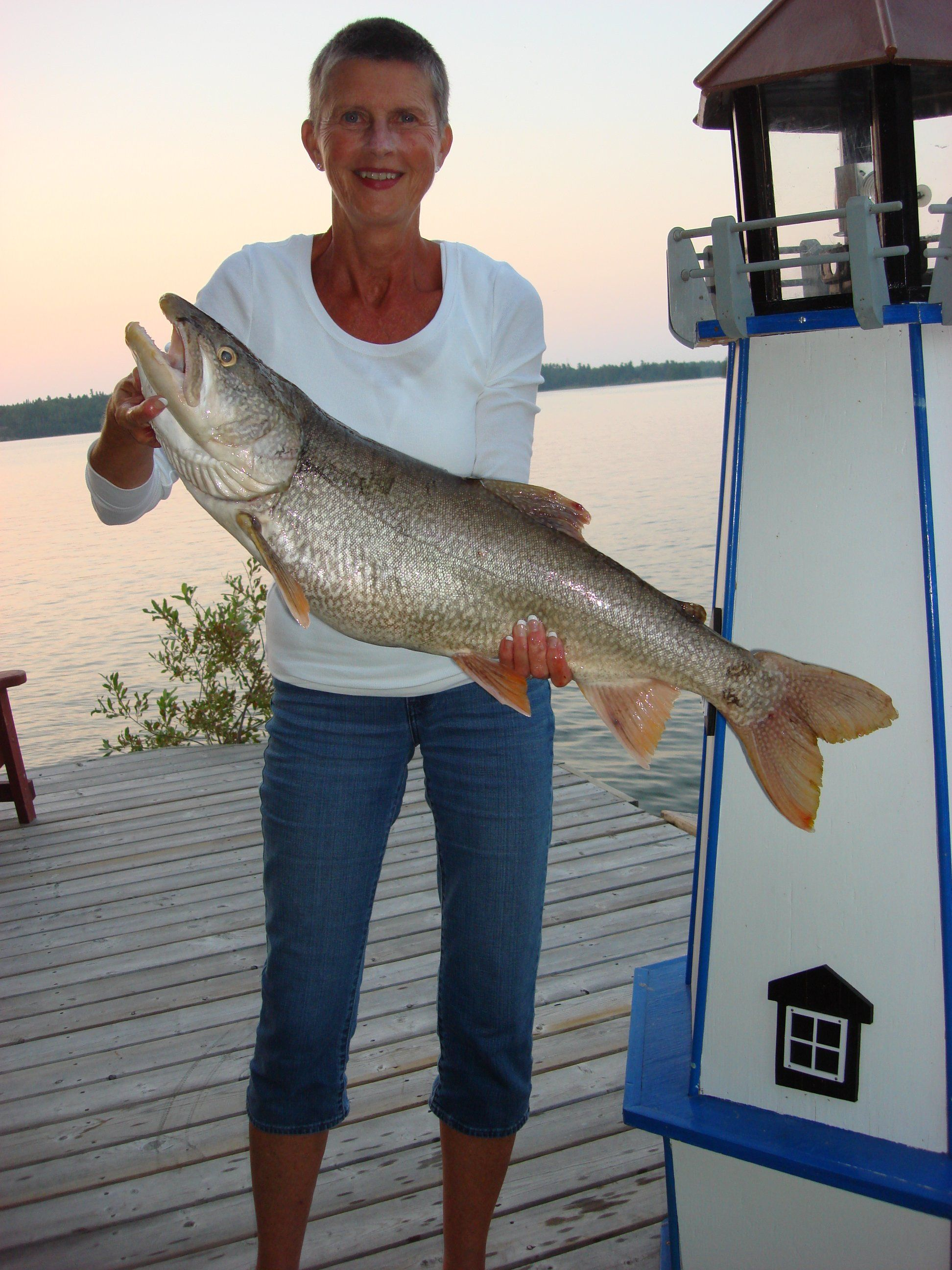 """Jeff Mohr took this photo of Janet Mohr and her lake trout at Tomahawk Resort on Lake of the Woods in Sioux Narrows, ON. Photo entry for the NOSFC's """"Best Fishing Photo"""" Contest."""