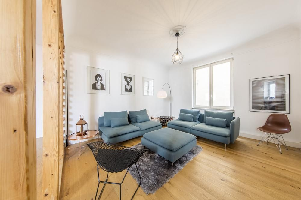 Wohnzimmer Mit Couch Gruppe In Blau Sowie Grauem Teppich, Dielenboden Und  Großem Fenster.