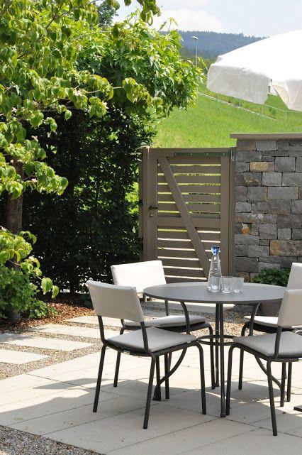 sitzplatz im hinterhof mit natursteinmauer als sichtschutz hohem gartentor und einem stilvoll. Black Bedroom Furniture Sets. Home Design Ideas