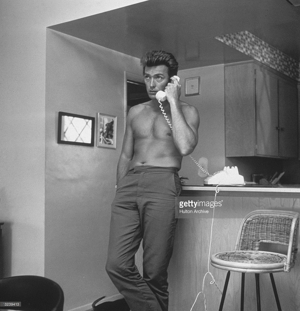 American Actor Clint Eastwood Leans Against A Kitchen Counter