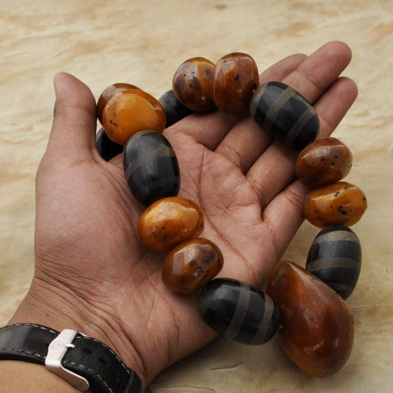 This old vintage necklace is made of golden honey amber and Dzi wood beads. This necklace is made by a local artisan from Kathmandu, Nepal,