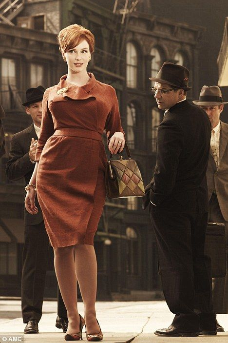 55ed6ca2ba6 Eye-catching  Christina Hendricks dazzles her male admirers in a scene from Mad  Men