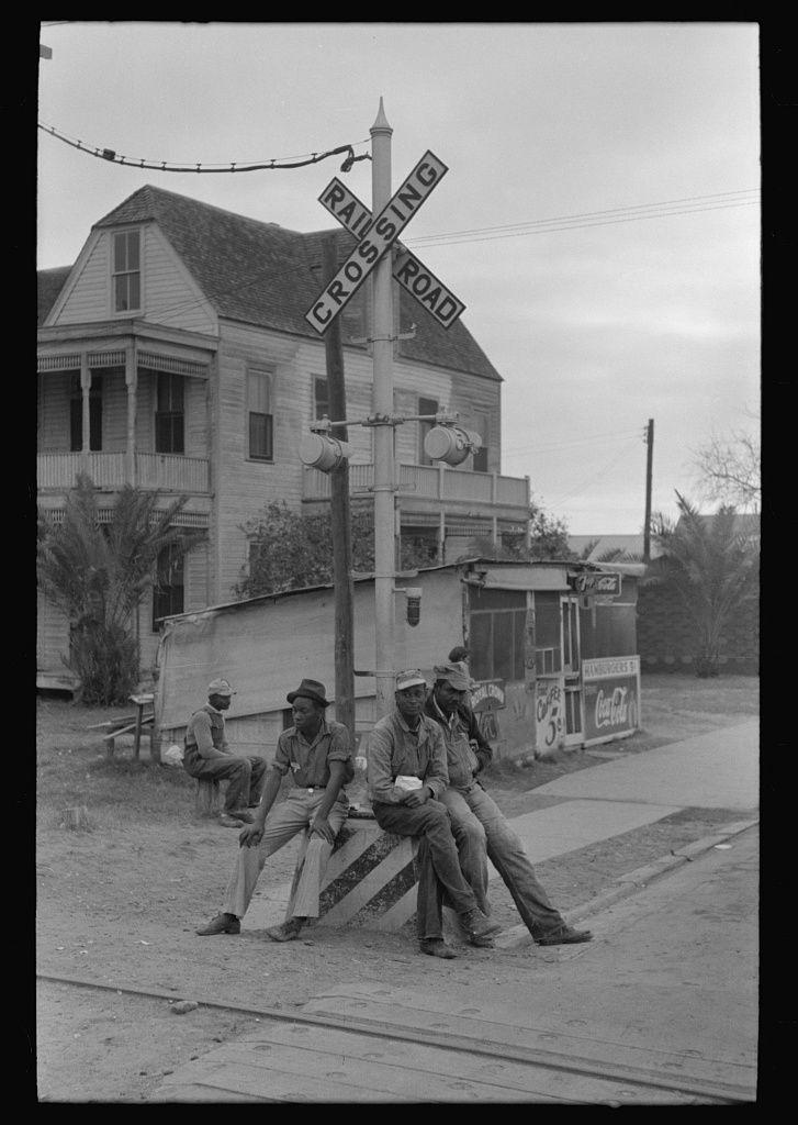 Negroes sitting on railroad crossing signal, Raymondville