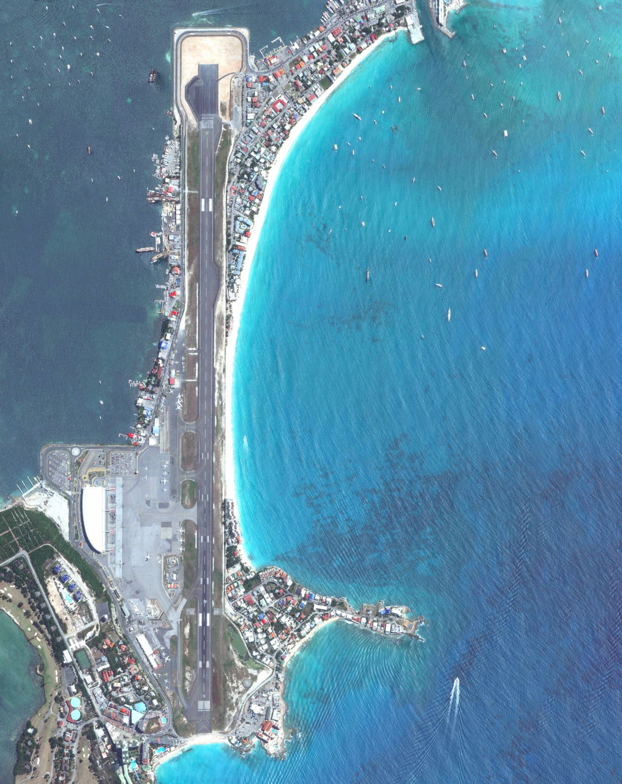 Princess Juliana International Airport is the main airport on the Caribbean island of Saint Martin. The airport is well-known for the approach to Runway 10, seen at the bottom of this Overview. Here arriving aircraft must have a 3° glide slope, flying at a shockingly low altitude over people relaxing on Maho Beach, to land safely.