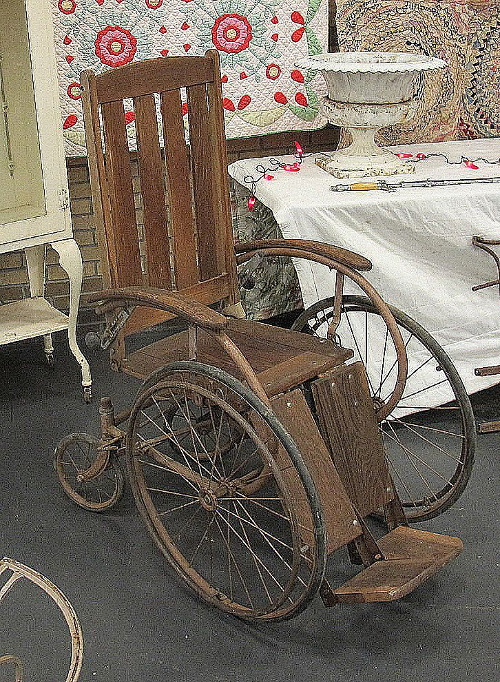 Old wooden wheel chair our booth full or unique