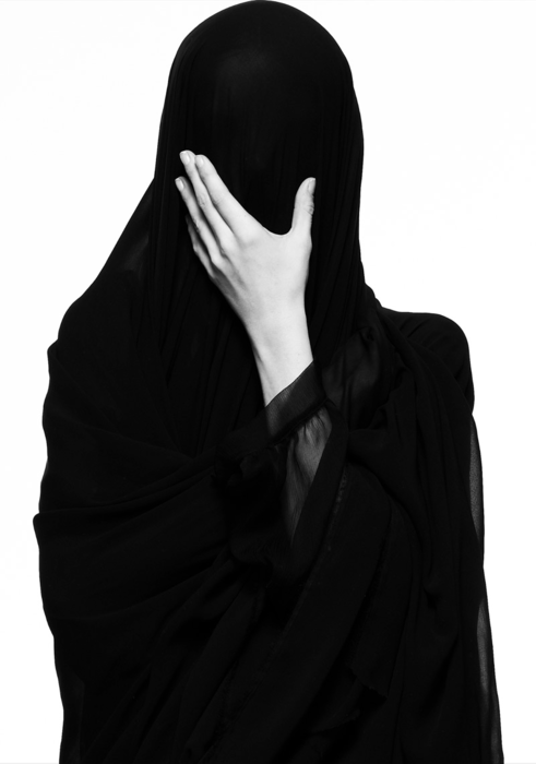 sorrow - woman covered entirely in black, holding hand to her face