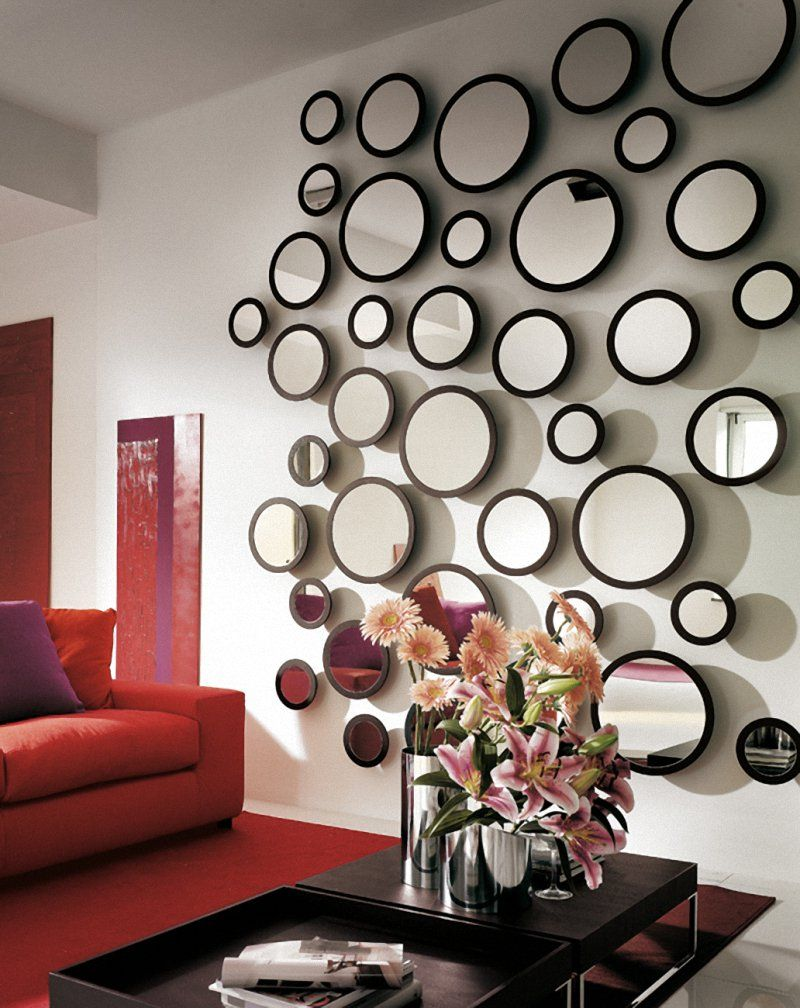 Astounding chic living room design with red sofas and stylish black glass coffee table with artistic round mirror with variant of sizes design for cool wall