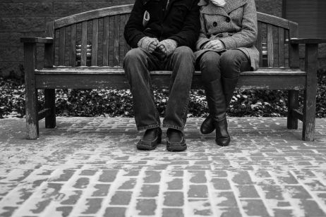 Outdoor engagement session on a bench in winter. This couple loves the public library, and even brought their crossword book along! Black and white photography idea. by Awakened Light Photography, Michigan photographer.