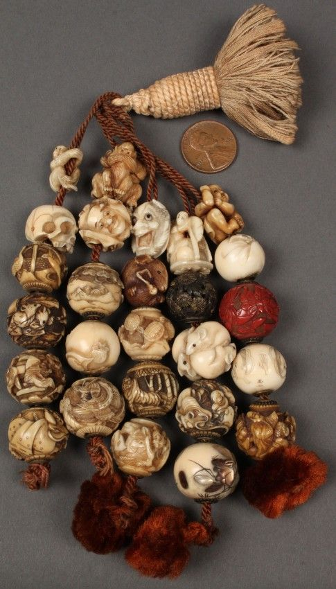 a collection of 26 Asian ojime beads,carved from ivory, bone, celluloid,cinnabar strung on a tassel depicting a tiger , skull, devil faces, rats , flying crane, butterfly . These were all collected by George and Charles Mitchell during the course of several trips to China and Japan in the late 19th century.