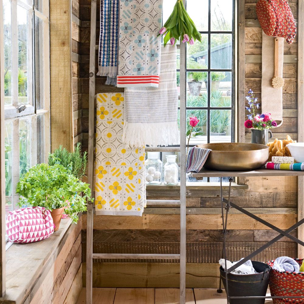 Countrystyle bathroom with vibrant towels and ladder storage