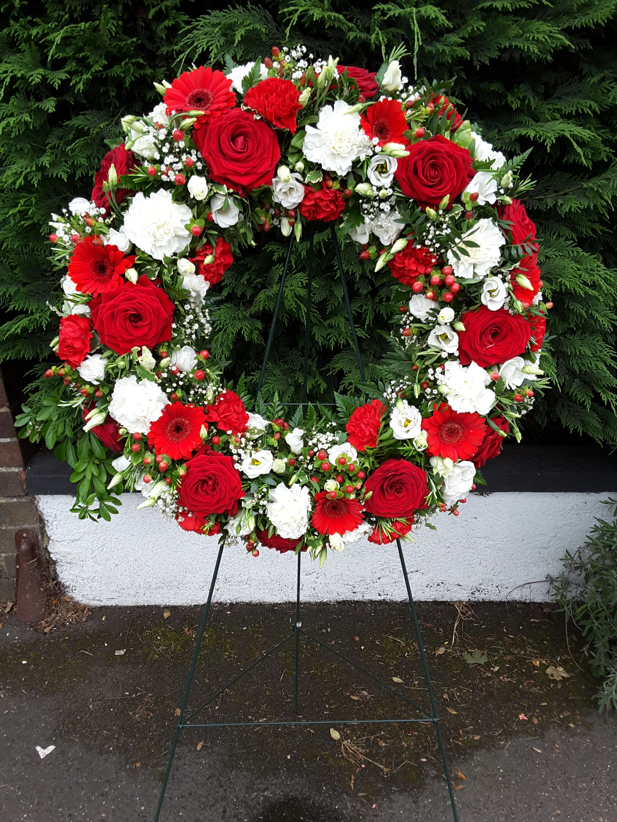 Wreath, in reds and whites, on a stand. Wreaths, Same