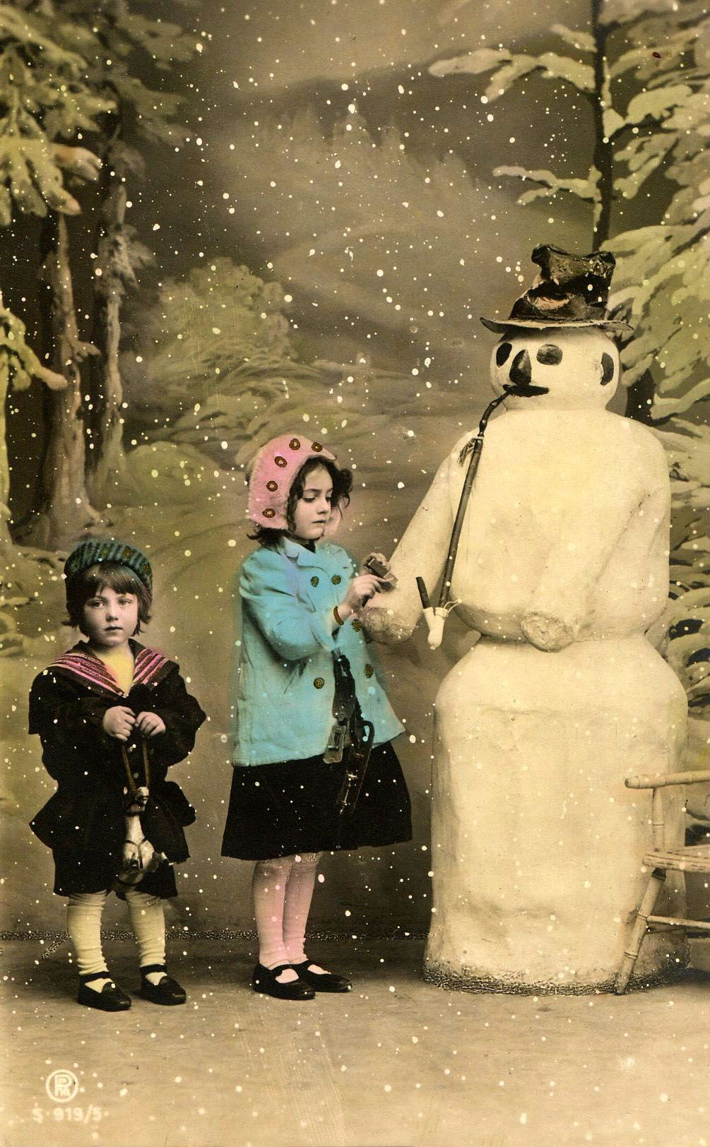 hand-tinted old postcard of winter scene - two children with snowman