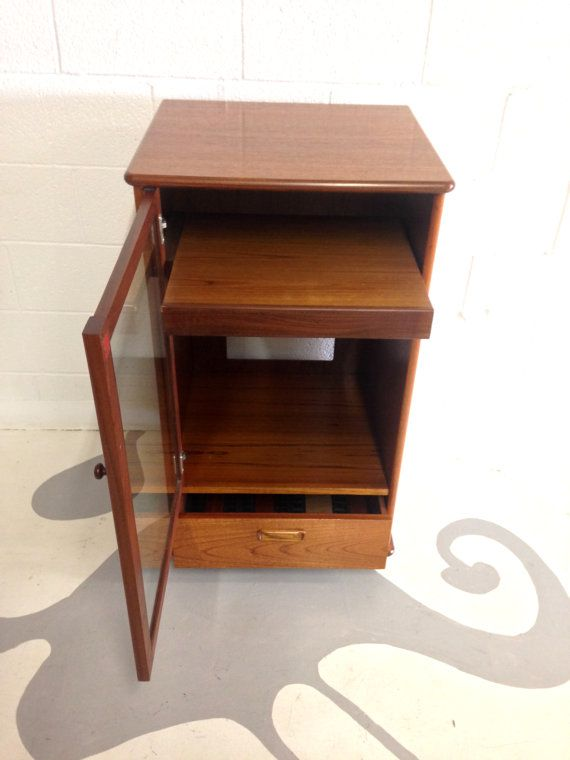 Mid Century Modern Stereo Cabinet In Teak With Glass Door And One Drawer  With Small Wheels Dimensions: W 22 D 20 H 381/2 Used: An Item That Has Been