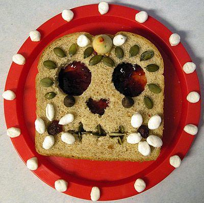 Sugar Skull (Calavera) Sandwich.    Bread + Peanut Butter & Jelly + Mini Marshmallows + Assorted Decorations / Pan + manteca de cacahuete con mermelada + esponjitas + pipas y almendras.