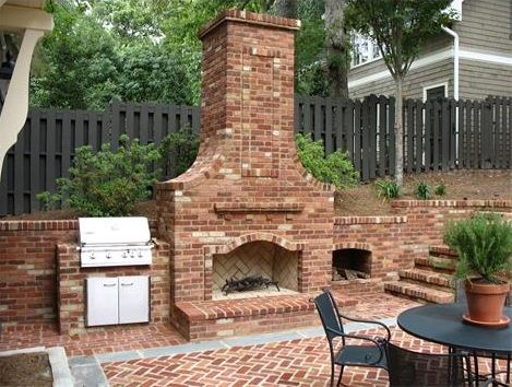 An Outdoor Fireplace With Built In Grill And Wood Storage