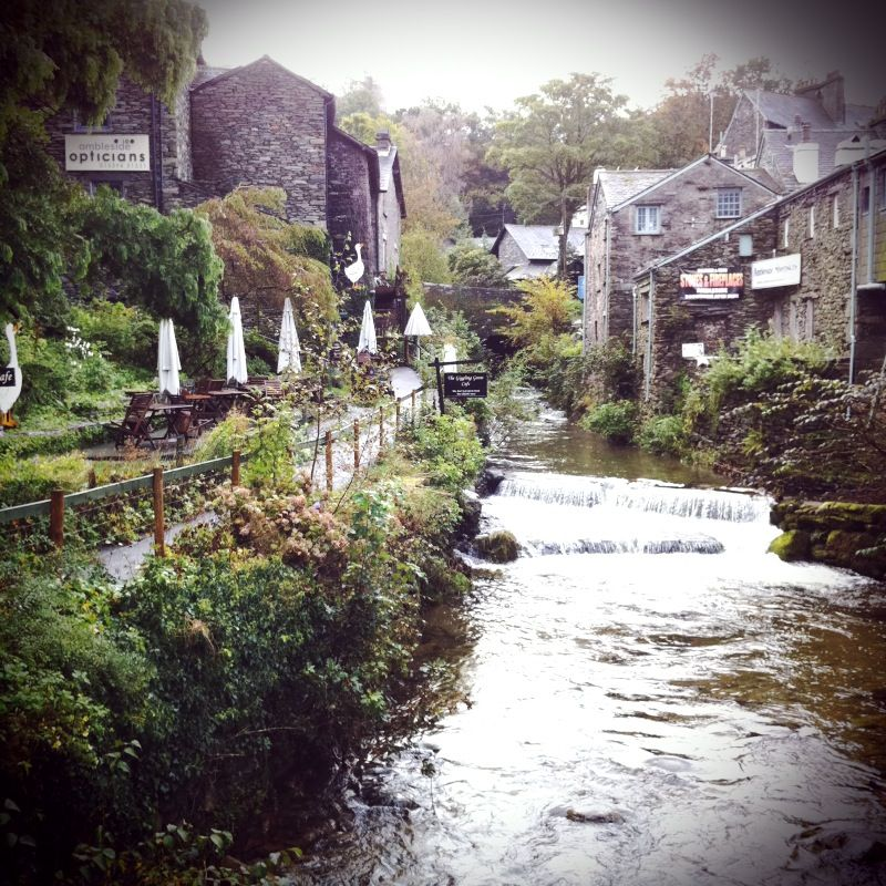 The Lakes District in England.  Waterfall, greenery, outdoor eating, old stone houses.