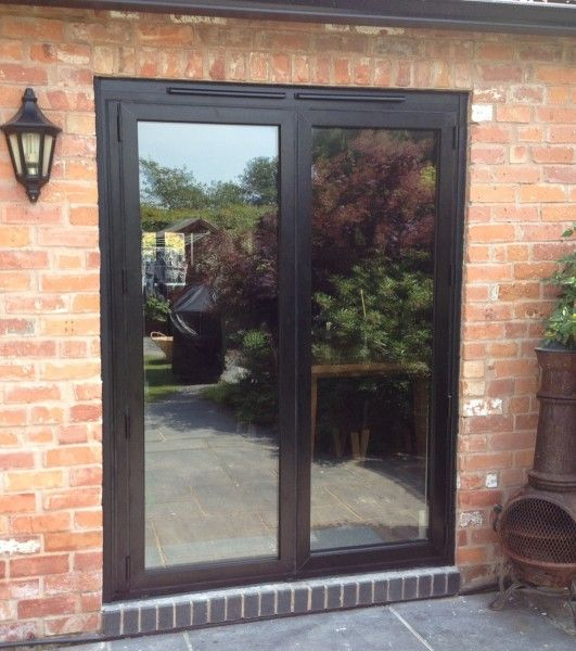 a small set of black bifolding doors on a garden terrace