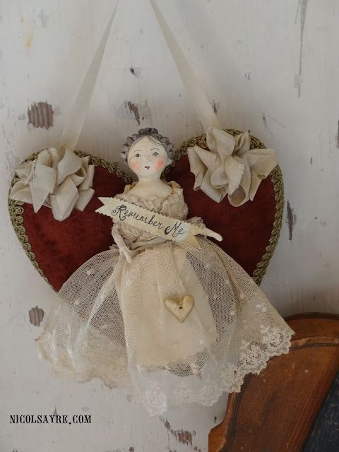 """Nicol Sayre Doll Shoppe - 13-FEB-2017. Little Love is a tiny 6"""" hand-sculpted papier mache on cloth body doll. She is dressed in antique net lace with a sweet sentiment banner and tiny gold heart charm. She is affixed to a large heart of antique velvet rimmed with metallic braid and ribbon bows."""