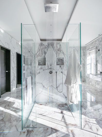 The Shower  The walls of the shower stall were originally planned in marble but modified to glass to let in more light. The marble was cut so precisely that when the slabs were joined alongside one another, the surface veining has a mirror-image butterfly effect. Photo: Nikolas Koenig
