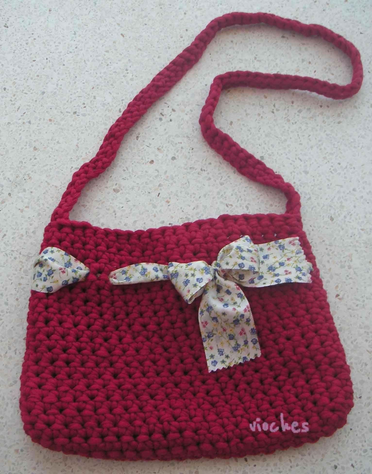 El bolso color cereza de tamaño grande, también es de tipo bandolera. Lo decora un lazo de flores en tonalidades azules.