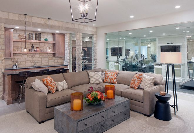 Basement living room opens to a glass enclosed gym basement gym