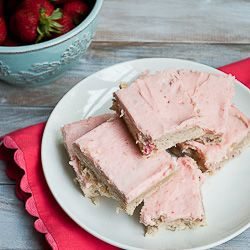 Strawberry sugar cookie bars topped with a fresh strawberry frosting