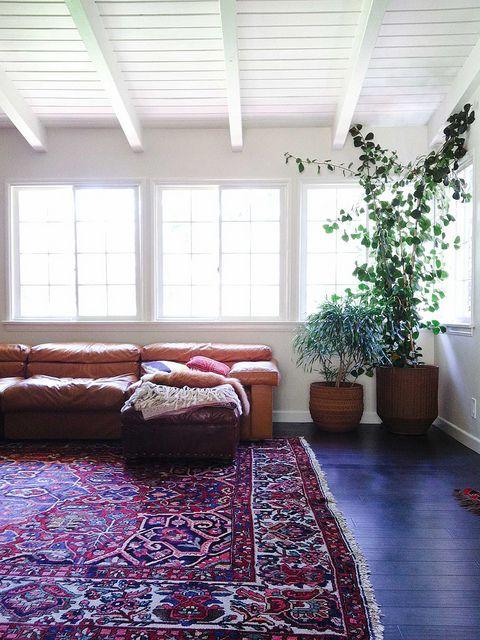 Tan leather sofa with oriental kilim rug