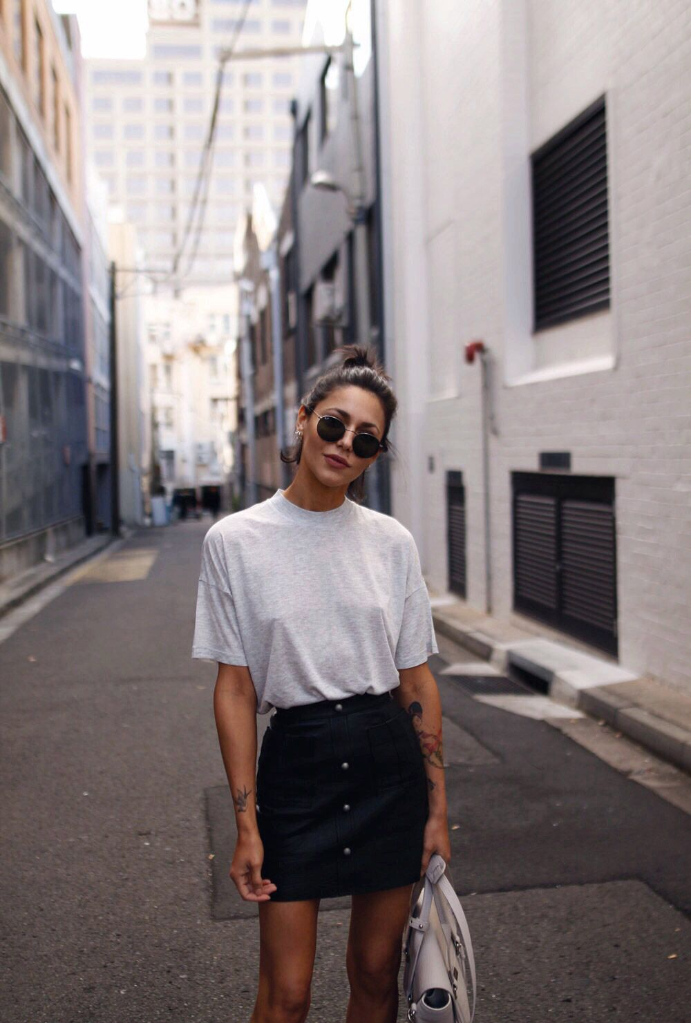 Simple outfit for spring - button up skirt, plain tee shirt, high bun and sunglasses