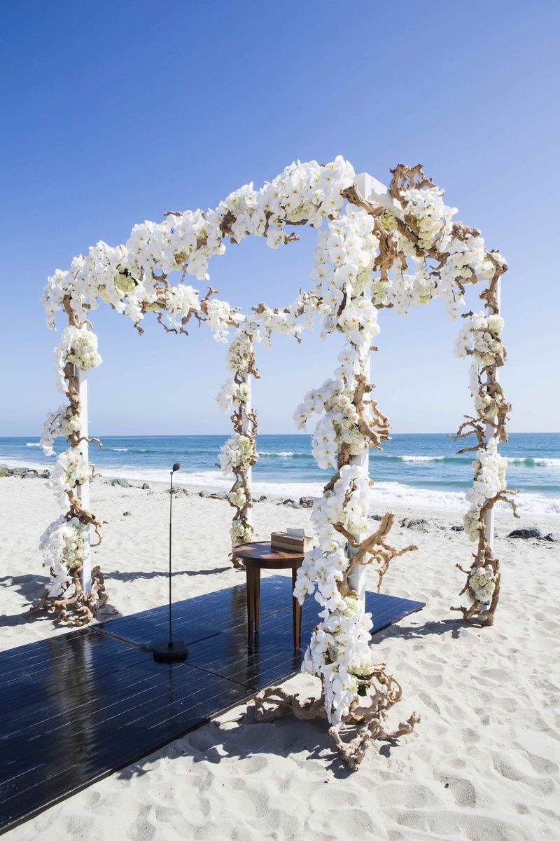 Floral-Embellished Altar    Photography: Samuel Lippke Studios   Read More:  http://www.insideweddings.com/weddings/elegant-summer-beach-wedding-in-southern-california/537/