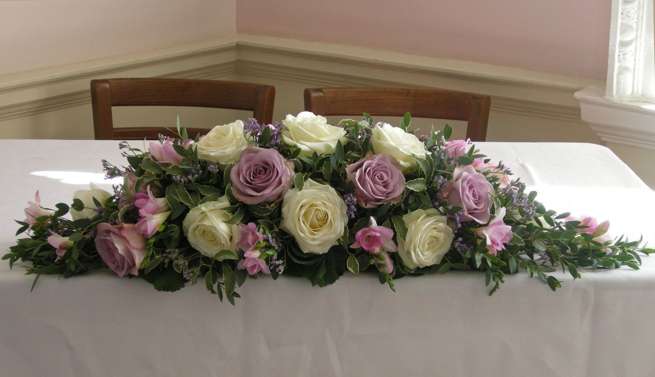 Ceremony Table Flower Arrangement Of Ivory Avalanch Roses, Dusky Lilac  Roses, Memory Lane,