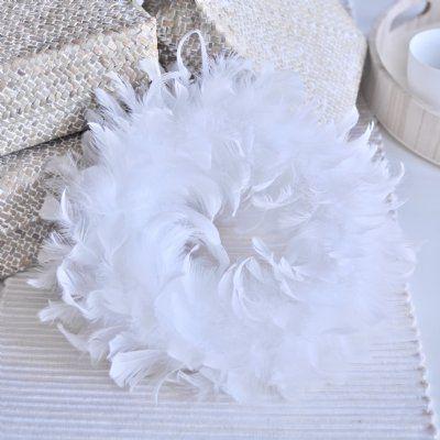 Ljuvlig vit fjäderdekorerad krans, går även att hänga.