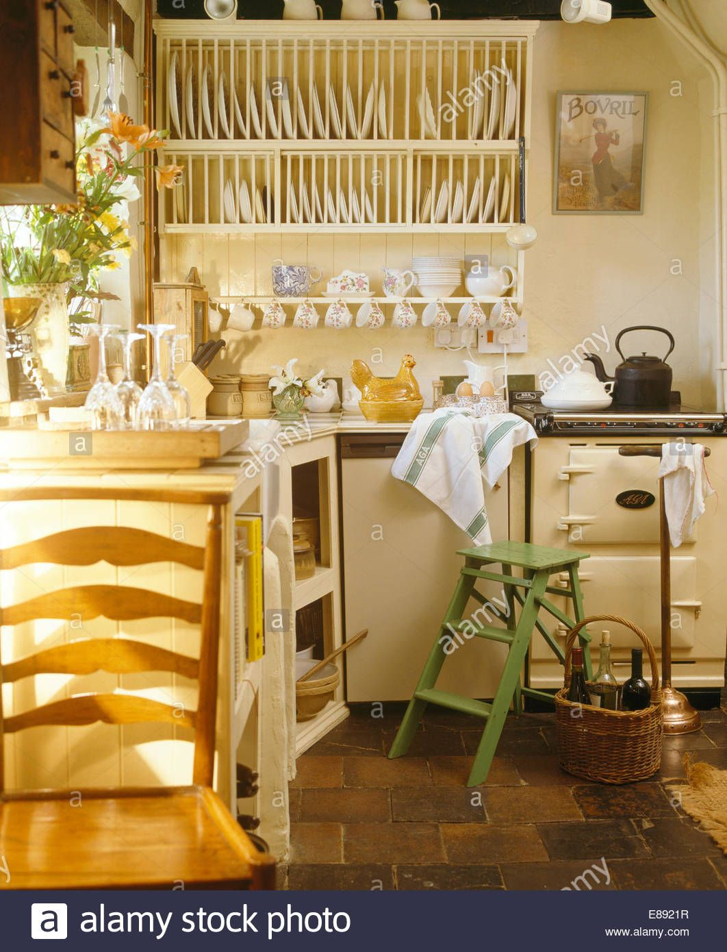 Plate rack on wall beside cream Aga oven in cream cottage kitchen ...