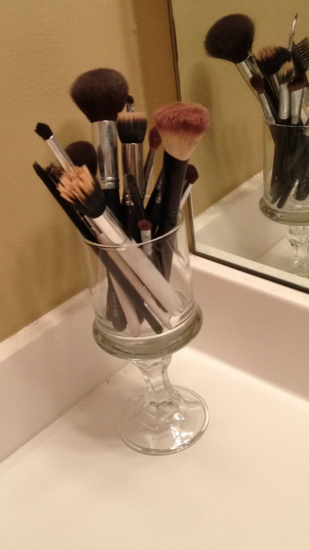 DIY makeup brush holder with a candlestick and a glass cup