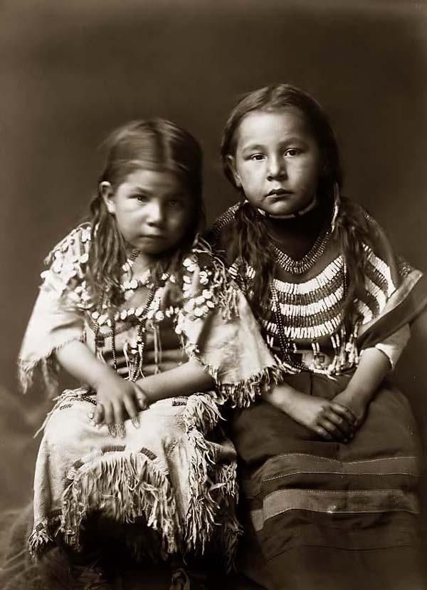 You are viewing a rare image of Bull Shoes Children, two small indian girls. It was taken in 1910 by Edward S. Curtis.    The image shows Two girls, full-length, seated, facing front, with loose hair, one wearing buckskin dress decorated with elks' teeth, one wearing beaded cloth dress