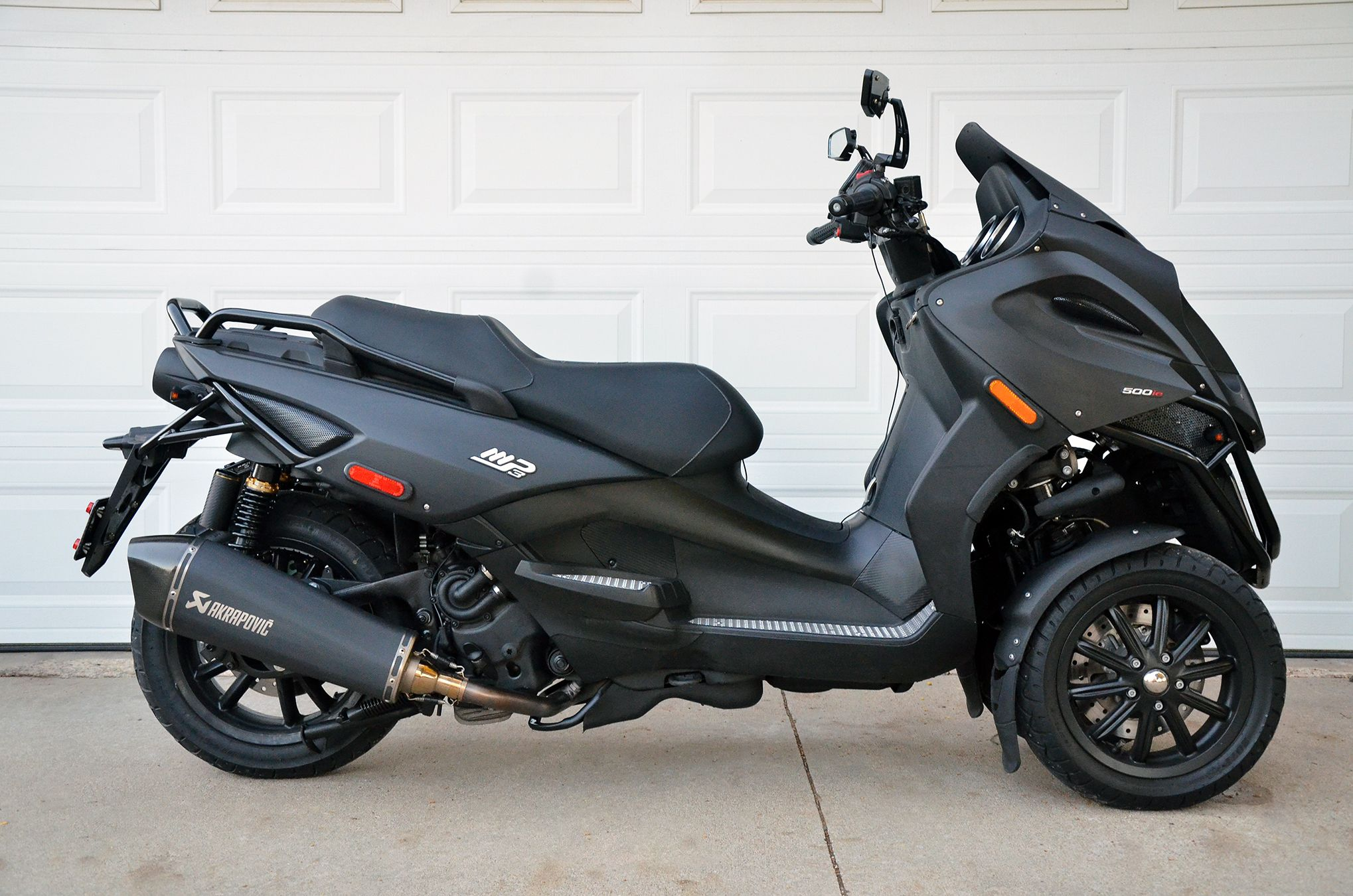 My custom '09 Piaggio MP3 500ie / Gilera Fuoco 500. Added lowered nitrogen shocks in the back, Akrapovic exhaust, custom mirrors & LED blinkers. Blacked out belly pan, swing arm & engine. Painted body panels in Rust-oleum Flexi-dip rubberized paint.