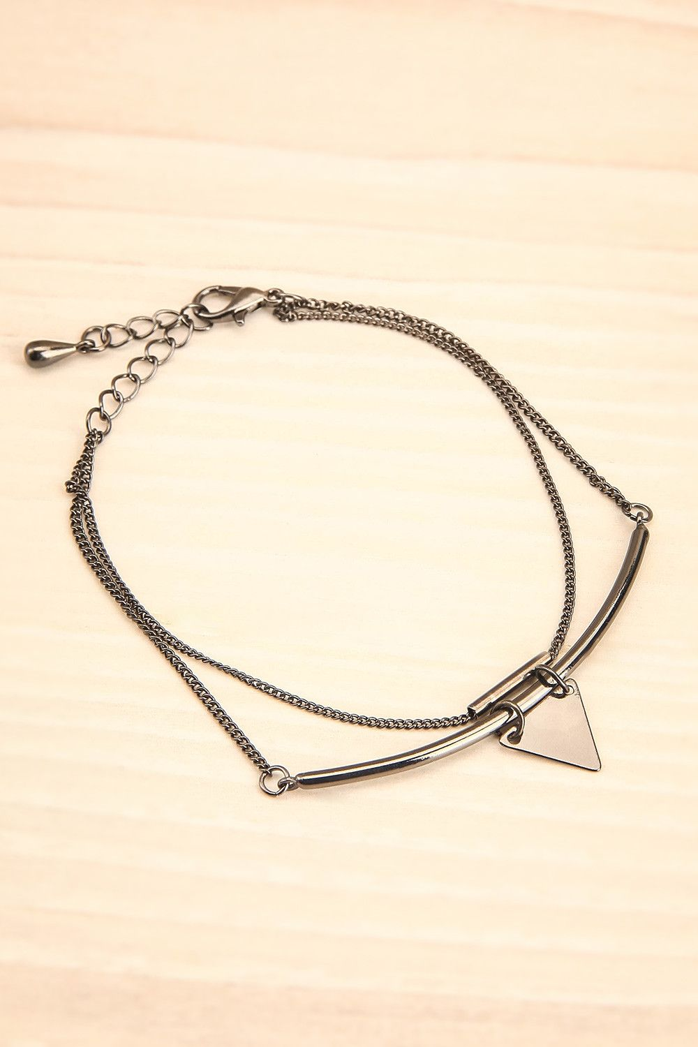 Le triangle à son poignet symbolisait l'équilibre du monde. The triangle on her wrist was a symbol for the balance of the world. Silver double chain and triangle bracelet www.1861.ca